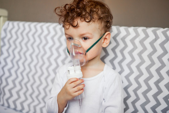 inhalation of the respiratory tract. baby sits with a nebulizer in his mouth, inhaler, treatment of bronchitis.
