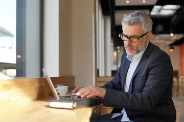Businessman working with computer waiting in modern airport