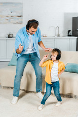 father with preschooler son in headphones listening music and dancing at home