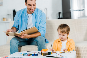 smiling father reading book while cute preschooler son drawing at home