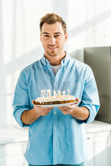 handsome man looking at camera and holding birthday cake with burning candles at home in morning