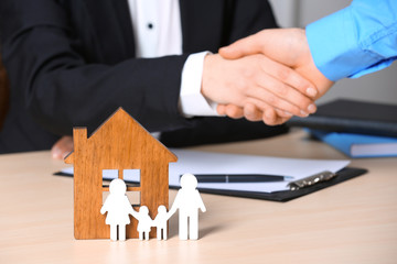 Man shaking hands with real estate agent at table, focus on family and house figures. Home insurance