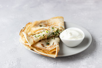 Thin pancakes or crepes with egg, green onion and natural yogurt or sour cream. Breakfast or brunch. Light concrete background. Copy space.