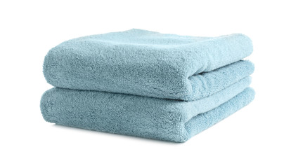 Folded clean soft towels on white background