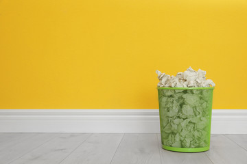 Metal bin with crumpled paper against color wall, space for text