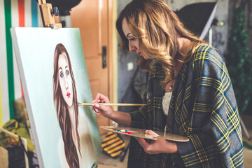 Artist paints picture on fabric with acrylic paints in her workshop