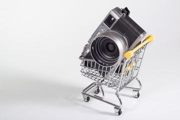 A camera in a small shopping cart at the white background. Selling photo technics, ideas of purchases. Close-up