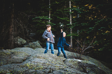 Young boys standing on rocks and throwing snow in the mountain forrest.