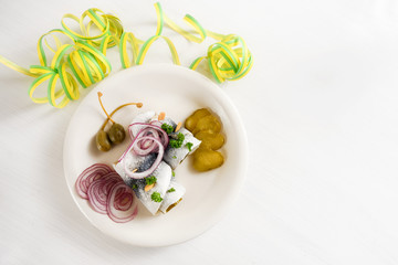 hangover meal, rolled pickled herring, also called rollmops with red onions, gherkins and capers on a white table with paper streamer, high angle view from above, copy space