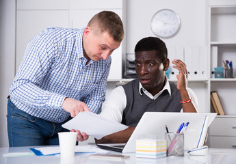 Interracial men working in office room with documents