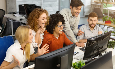 Business team looking at screen of computer celebrating victory
