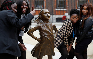 Students from some of London's all girls' schools, pose for pictures with the 'Fearless Girl' statue unveiled by State Street in the financial district of London