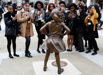 Students from some of London's all girls' schools, take pictures of the 'Fearless Girl' statue unveiled by State Street in the financial district of London
