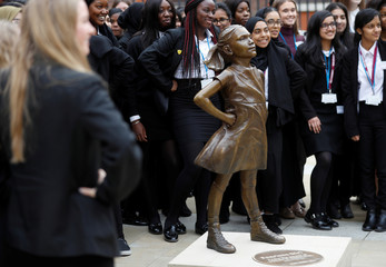 Students from some of London's all girls schools, pose for pictures with the 'Fearless Girl' statue unveiled by State Street in the financial district of London