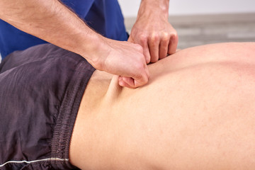 Close-up of man's back and hands of chiropractic.  Physiotherapy, osteopathy, sports injury rehabilitation. Manual testing over the dorsal spine, pull and roll, skin rolling, facia pulling. Massage.