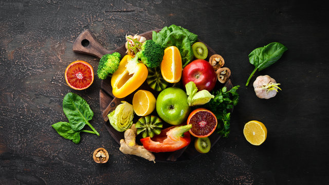 Food containing vitamin C: Orange, lemon, apple, rose, garlic, broccoli, apple, kiwi, spinach. Top view. On a brown background.