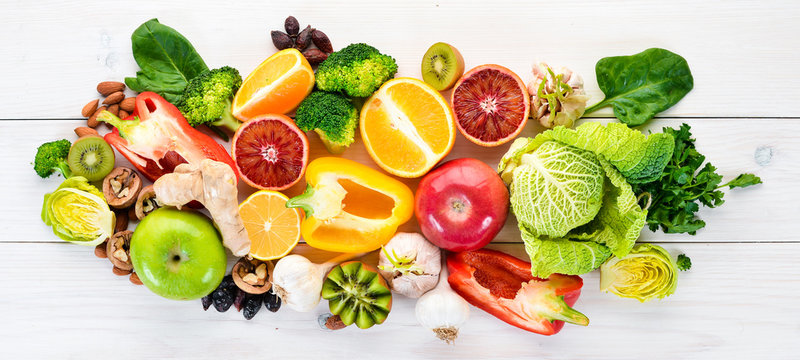 Food containing natural vitamin C: Orange, lemon, apple, rose, garlic, broccoli, apple, kiwi, spinach. Top view. On a white background.