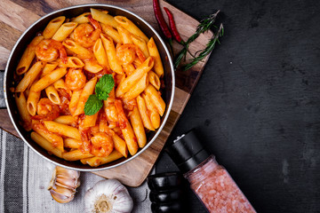 penne pasta with shrimps, tomato sauce   in a black frying pan with spice ,top view.