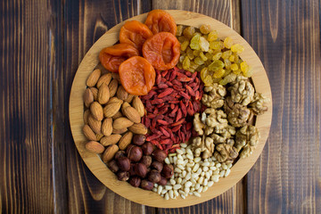 Dried apricots, raisins, goji berries ,different nuts on the round cutting board on the brown  wooden background.Top view.