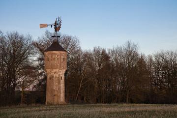 Windmühle auf einem Turm vor einigen Bäumen in der Landschaft am Abend