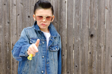 Elvis kid,Boy child dressed as 1950s style greaser ,rockabilly wearing denim jacket with pompadour slicked back ,jet black hair.