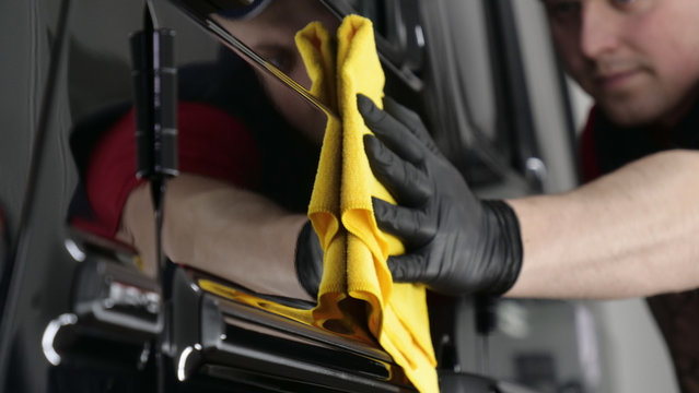 Professional worker guy (Man) wipes the car after painting (ceramics) in a special uniform with black gloves and with a yellow rag. Concept of: Young master, Preparing for the sale, Cleaning.