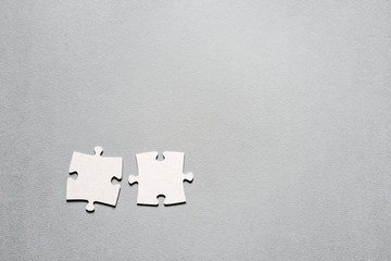 Two puzzle pieces on a gray surface, closeup, top view. Business concept