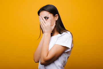 Pretty young caucasian female dressed in white shirt looking through the hand surprised of what she is seeing against yellow background. Wall mural