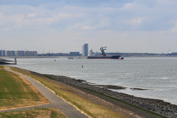 a ship is unloaded at high seas in holland with the skyline in the background