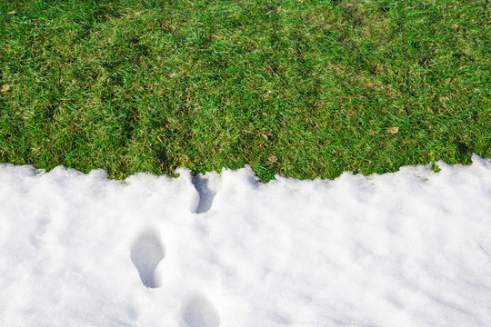 Welcome spring. Goodbye winter. Fresh human boots footprints in white melting snow. Empty place for text, quote or sayings on green grass.
