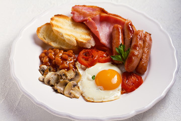 Full English or Irish breakfast with sausages, bacon, eggs, tomatoes, mushrooms and beans. Nutritious and healthy morning meal.