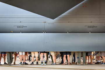 Queue of people, partially hidden be fuselage of aircraft