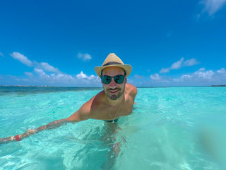 Hispanic young man taking a selfie picture in a tropical beach at San Andres, Colombia