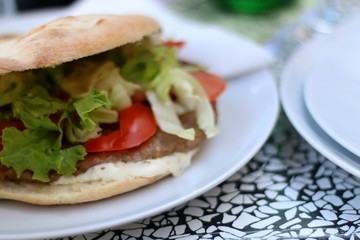 Burger in a flatbread bun with meat, lettuce, tomatoes and mayonnaise. Selective focus.