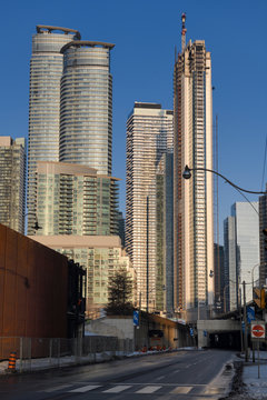 Empty Lakeshore Boulevard in downtown Toronto with new highrise condominium towers at sunset in winter with blue sky