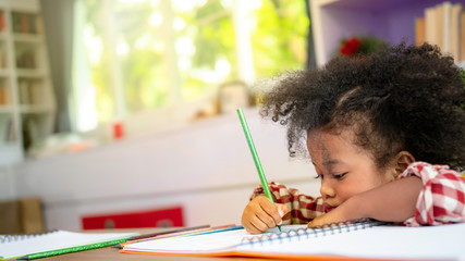 Cute little African American kid concentrate draw full colour of picture with colour pencil in living room or home school with burred window background, Kindergarten school concept, education concept.
