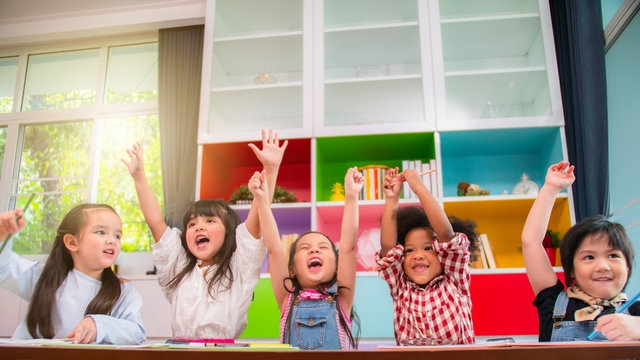 Group of multi-ethnic five little kids children African American, asian and Caucasian happiness together with friend to draw colour pencil to full colour of picture in living room or class room