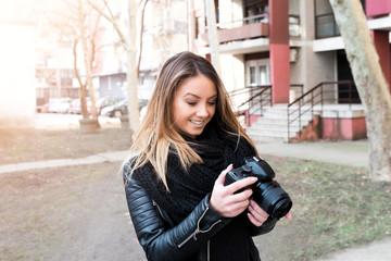 Young girl holding camera outside