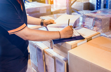 Warehouse worker writing on clipboard with checklist details shipments boxes, Warehouse inventory managemant.