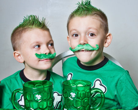 Twin brothers Irish boys with green mohawks and mustaches , ready for St Patrick's Day