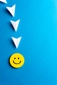 Emoticon yellow happy smiling face with paper airplanes on blue background. Social media, send and sharing concept. Content marketing concept.
