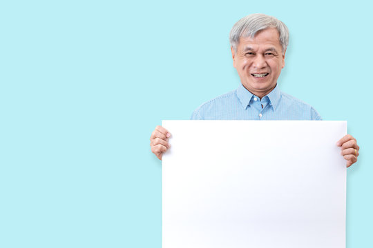 Happy grandpa smiling with white teeth, enjoy moment and holding a blank board. Asian older man showing white blank board for your advertising text message or promotional content.
