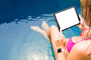 Woman sitting by the pool and using tablet computer. Horizontal screen orientation.