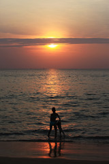 Silhouette of adorable little girl on a beach at sunset