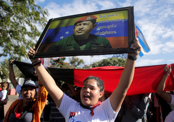 A supporter of Nicaraguan President Daniel Ortega holds a picture of late Venezuelan President Chavez during a march to commemorate his death anniversary and in support of the Bolivarian Revolution in Managua