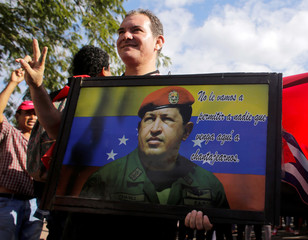A supporter of Nicaraguan President Ortega holds a picture of late Venezuelan President Chavez during a march to commemorate his death anniversary and in support of the Bolivarian Revolution in Managua
