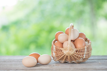 raw eggs in basket on wooden table outdoor