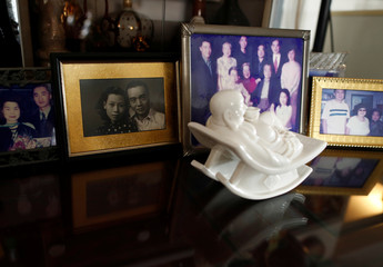 A black and white photo of hawker Leong Yuet Meng in her youth is pictured among her family photos at her home in Singapore