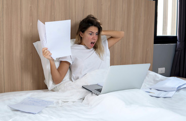 young blonde sitting in bed, works on laptop, iagitated holding hand on head,