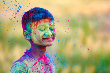 Indian child playing with the color in holi festival